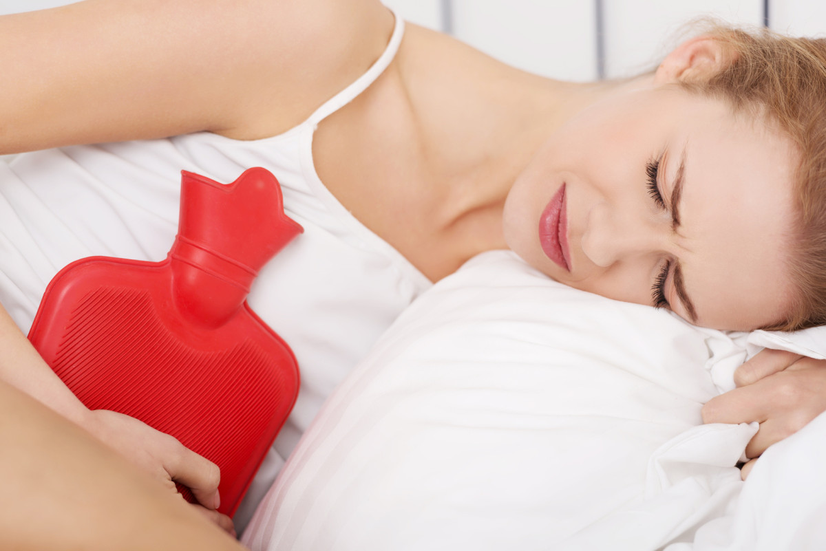 Woman with stomach ache holding hot water bottle